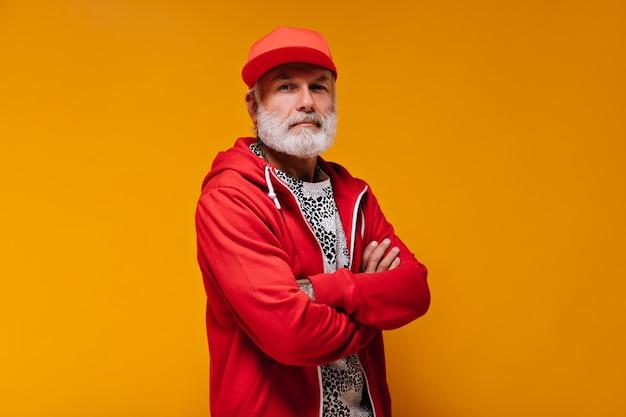 Portret mężczyzny w czerwonej czapce i bluzie z kapturem na pomarańczowej ścianie