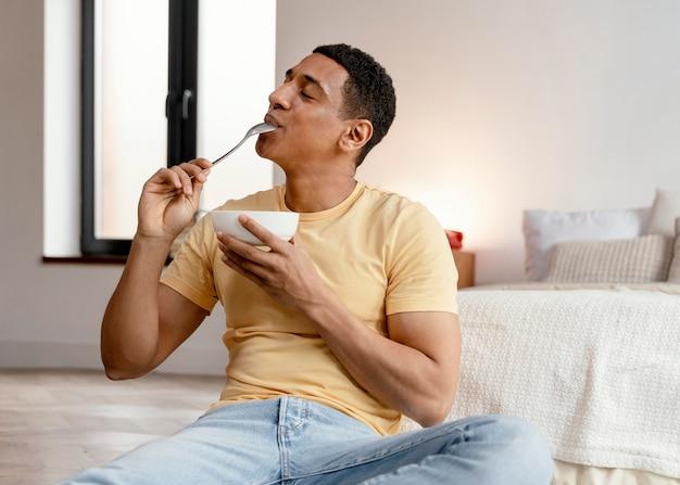 Portret mężczyzny w domu, jedzenie