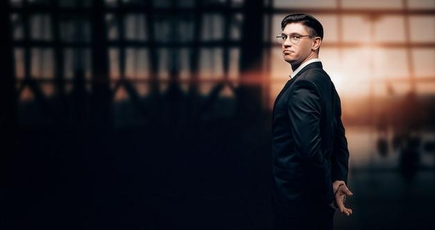 Portret mężczyzny w garniturze. stoi na lotnisku i patrzy w kamerę
