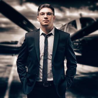 Portret mężczyzny w garniturze. stoi na lotnisku w sportowym samolocie. projektant samolotów. prywatne linie lotnicze. różne środki przekazu