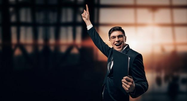 Portret mężczyzny w garniturze. stoi na lotnisku z podniesionymi rękami