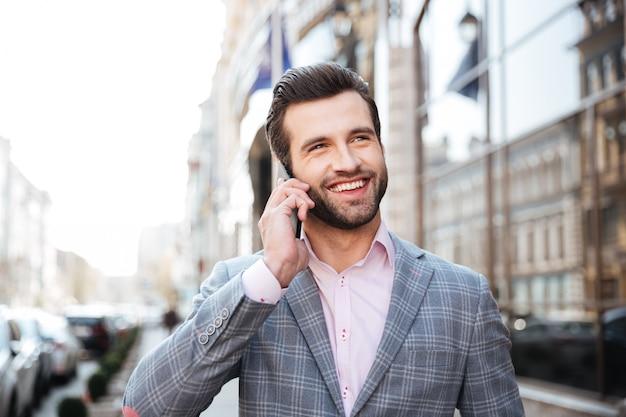 Portret mężczyzny w kurtce rozmawia przez telefon komórkowy