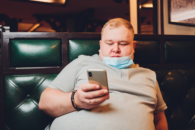 Portret mężczyzny w masce medycznej siedzi na kanapie w nowoczesnym domu