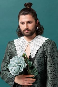 Portret mężczyzny w modnych ubraniach, trzymając kwiaty