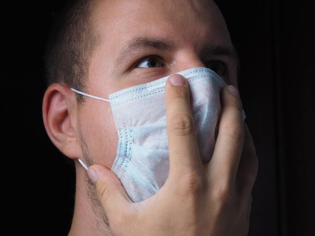 Portret mężczyzny w ochronnej masce medycznej z przestraszonymi oczami i dłonią przyciśniętą do twarzy. koncepcja medycyny, wirusy i lęki ludzi