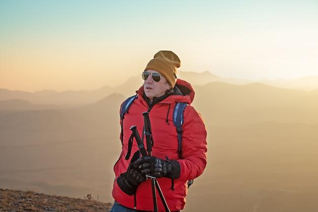 Portret mężczyzny w okularach przeciwsłonecznych z kijami do nordic walking i plecakiem wysoko w górach.