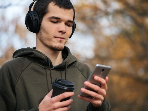 Portret mężczyzny w parku jesień ze słuchawkami. styl życia.