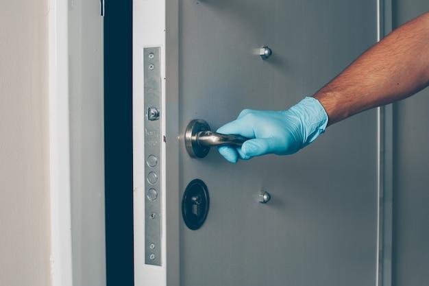Portret mężczyzny w pokoju otwierając drzwi rękami w rękawiczkach