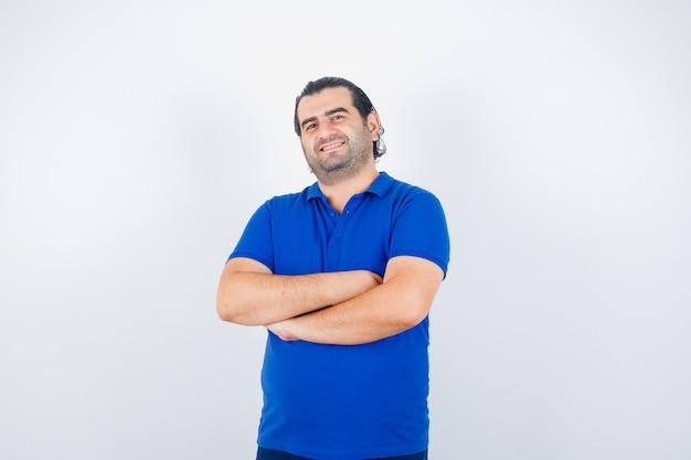 Portret mężczyzny w średnim wieku, stojącego ze skrzyżowanymi rękami w niebieskiej koszulce i patrząc szczęśliwy widok z przodu