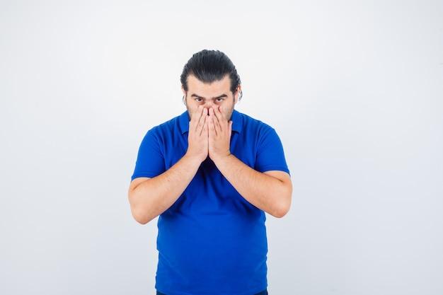 Portret mężczyzny w średnim wieku, trzymając się za ręce na ustach w niebieskiej koszulce i patrząc poważny widok z przodu