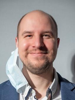 Portret mężczyzny w średnim wieku w kurtce i koszuli z maską ochronną wiszącą na jednym uchu.