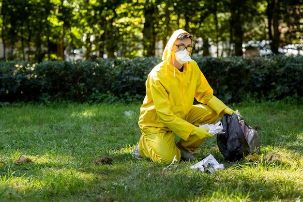 Portret mężczyzny w żółtym kombinezonie ochronnym i masce.