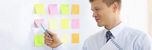 Portret mężczyzny wskazującego piórem na kolorowe notatki na tablicy. biznesmen przygotowuje się do rozmowy dyrektorów. koncepcja biznesowa i firmy