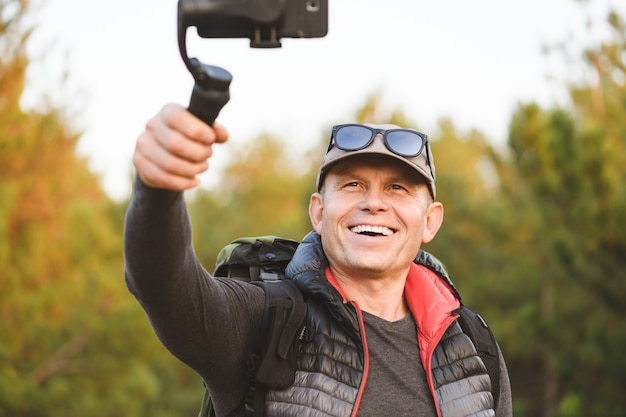Portret mężczyzny wykonującego zdjęcia i filmy z pięknych miejsc ze stabilizatorem na telefon komórkowy