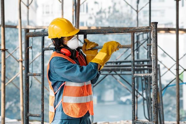 Portret mężczyzny z bocznym widokiem wyposażenia bezpieczeństwa przewożących drabinę