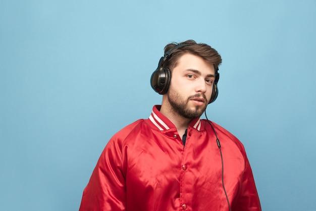Portret mężczyzny z brodą, ubrany w czerwoną kurtkę na niebiesko