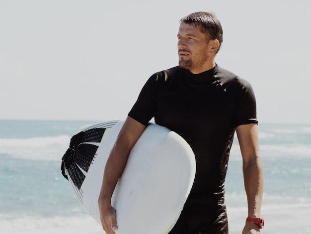 Portret mężczyzny z deską surfingową. przystojna młoda męska atlety mienia kipieli deska z mokrym włosy na lato plaży sporta wakacje. sportowy cel podróży. styl życia surfowania.