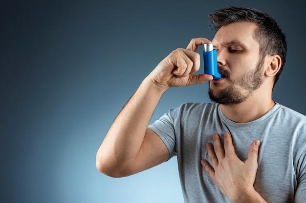 Portret mężczyzny z inhalatorem astmy w rękach, atak astmatyczny. pojęcie leczenia astmy oskrzelowej, kaszlu, alergii, duszności.