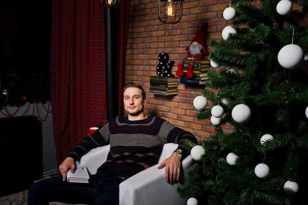 Portret mężczyzny z książką siedzącą na krześle przed choinka z dekoracjami.