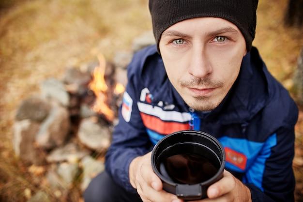 Portret mężczyzny z kubkiem gorącej herbaty w jego rękach