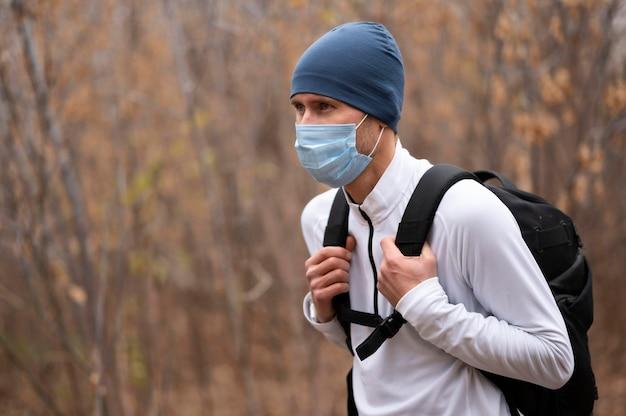 Portret mężczyzny z maską i plecakiem w lesie