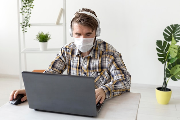 Portret mężczyzny z maską pracującą w domu