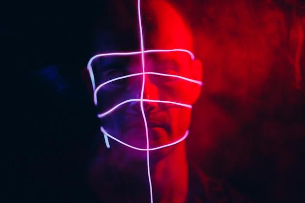 Portret mężczyzny z neonowymi liniami blasku na twarzy. pojęcie cyberpunk i wirtualnej rzeczywistości.