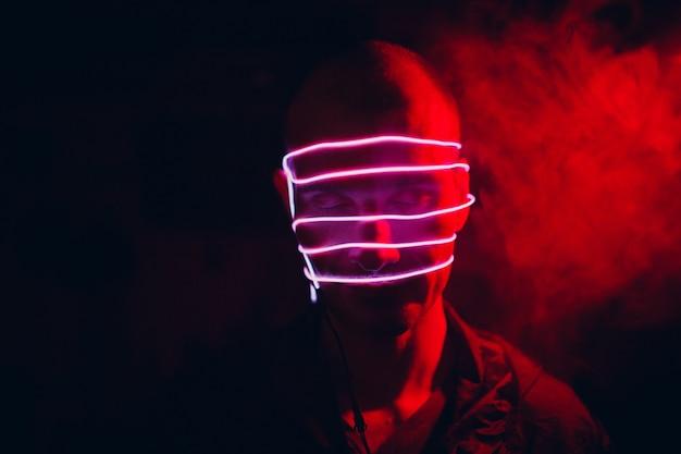Portret mężczyzny z neonowymi liniami rurki na twarzy w ciemności. pojęcie cyberpunk i wirtualnej rzeczywistości.