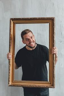 Portret mężczyzny z ramą na tle szarej ściany