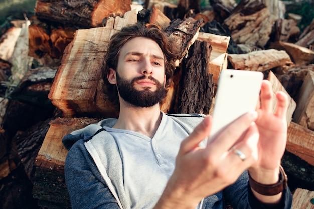 Portret mężczyzny z smartphone na stosie drewna.
