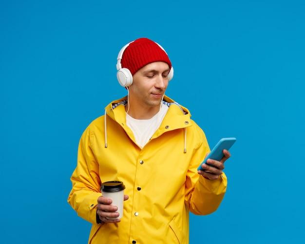 Portret mężczyzny z telefonem, słuchanie muzyki i picie kawy