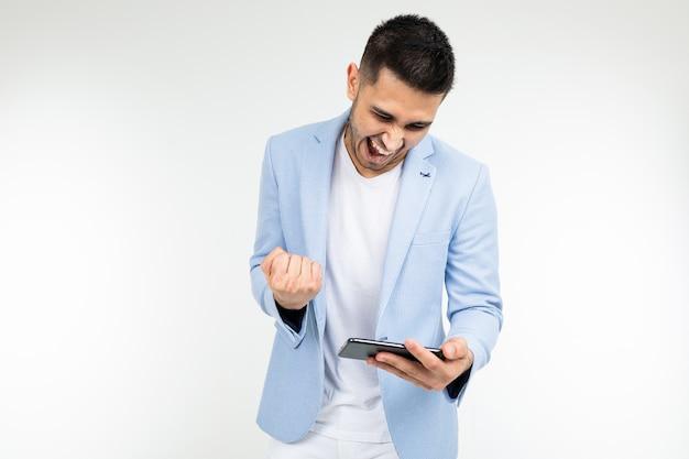 Portret mężczyzny z telefonem w rękach, grając w gry na białym tle.