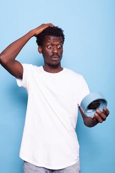 Portret mężczyzny z zegarem ściennym trzymającym rękę na głowie