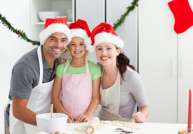 Portret mężczyzny z żoną i córką gotowanie świąteczne herbatniki