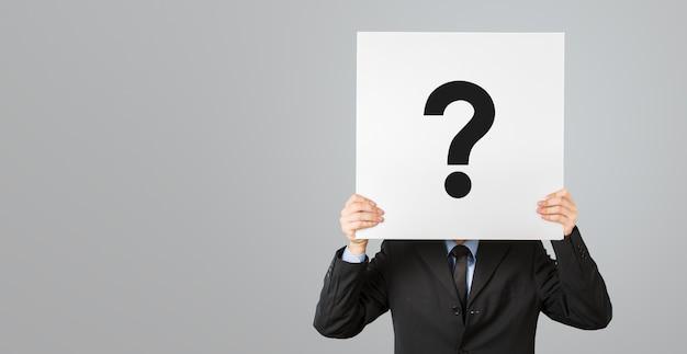 Portret mężczyzny, zaglądający za symbol przesłuchania. znak zapytania, symbol. zamyślony mężczyzna.