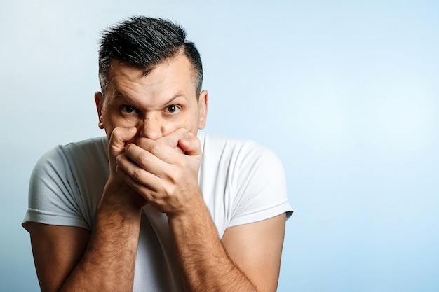 Portret mężczyzny, zakrywa usta dłońmi, cenzura, wolność słowa. pojęcie mowy ciała, ludzkich emocji, reakcji.