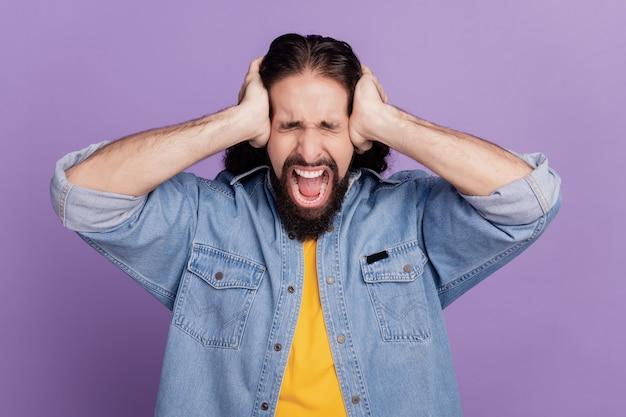 Portret mężczyzny zakrywa uszy na fioletowym tle krzyczeć z otwartymi ustami