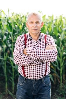 Portret mężczyzny ze skrzyżowanymi rękami w casualowej koszuli w gospodarstwie na tle pola kukurydzy