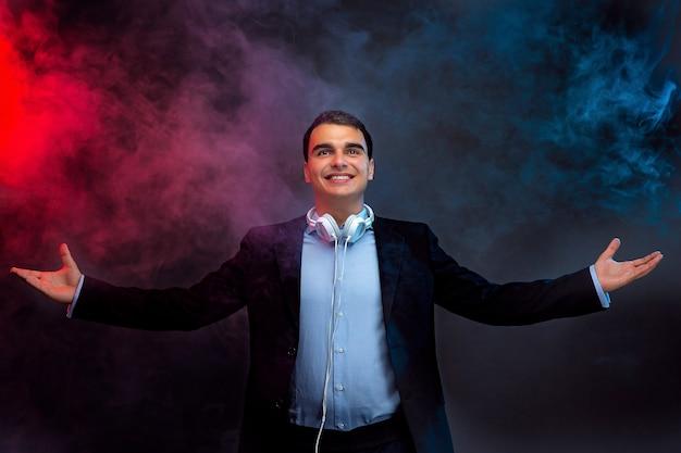 Portret mężczyzny ze słuchawkami na ciemnej ścianie z dymem.