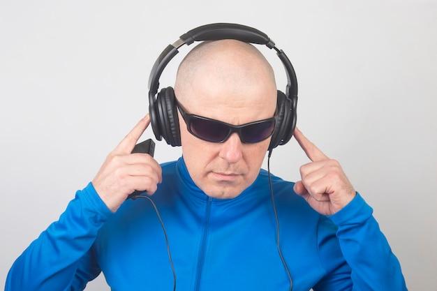 Portret mężczyzny ze słuchawkami na głowie i okularami przeciwsłonecznymi na białym tle