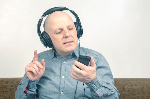 Portret mężczyzny ze słuchawkami w relaksie słuchającym ulubionej muzyki