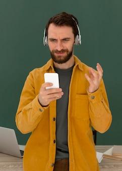 Portret mężczyzny ze słuchawkami za pomocą telefonu komórkowego