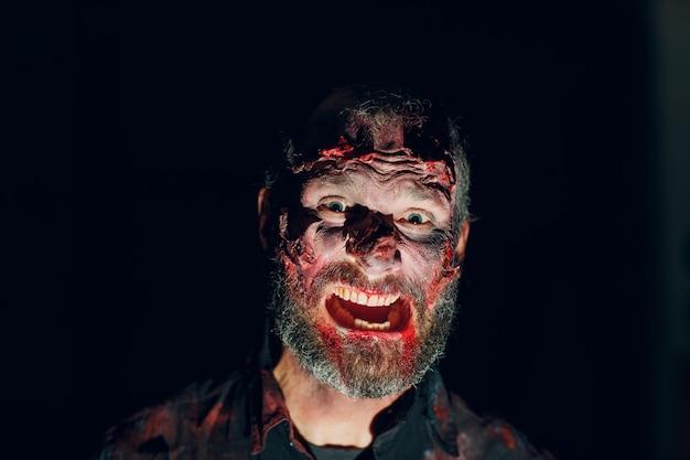 Portret mężczyzny zombie w ciemności z makijażem na imprezę halloween