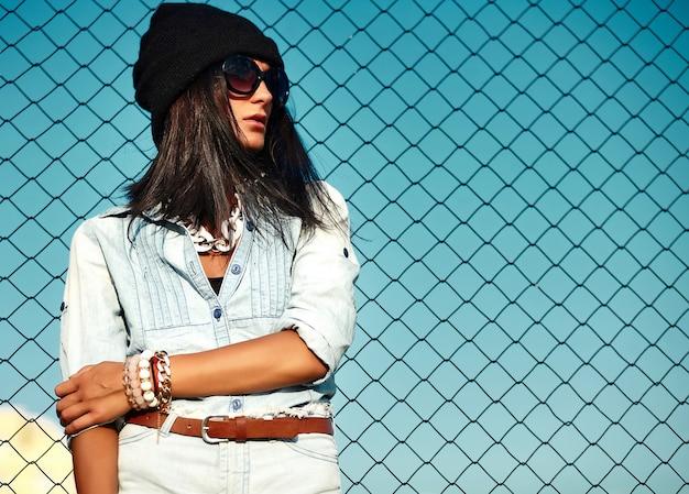 Portret miejski nowoczesny model młoda kobieta stylowa kobieta w dorywczo jeansy spodenki tkaniny na zewnątrz na ulicy w czarnej czapce