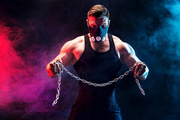 Portret mięśni sportowca łzawienie metalowy łańcuch. czarna ściana z dymem