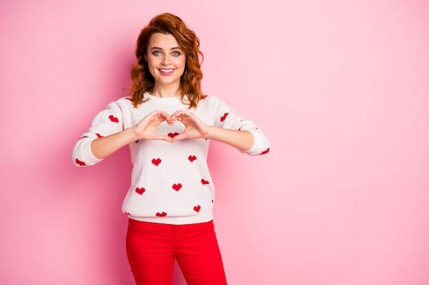 Portret miła atrakcyjna wesoła miła czuła dziewczyna ubrana w biały sweter przedstawiający symbol serca
