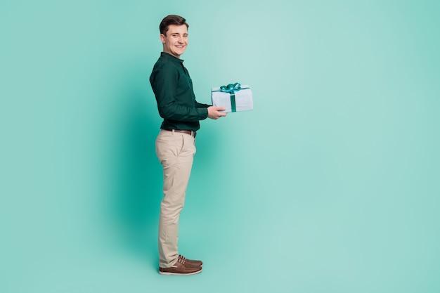 Portret miłego atrakcyjnego faceta trzyma obecne pudełko daje kopię pustej przestrzeni na turkusowym tle