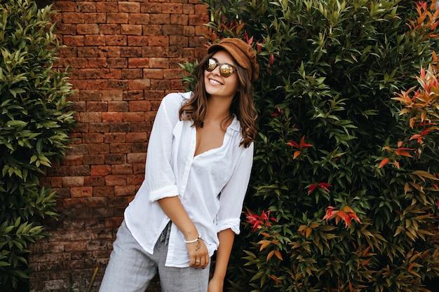 Portret miłej dziewczyny z falowanymi włosami. kobieta w czapce, okularach i lekkim stroju śmieje się z ceglanego budynku i roślin.