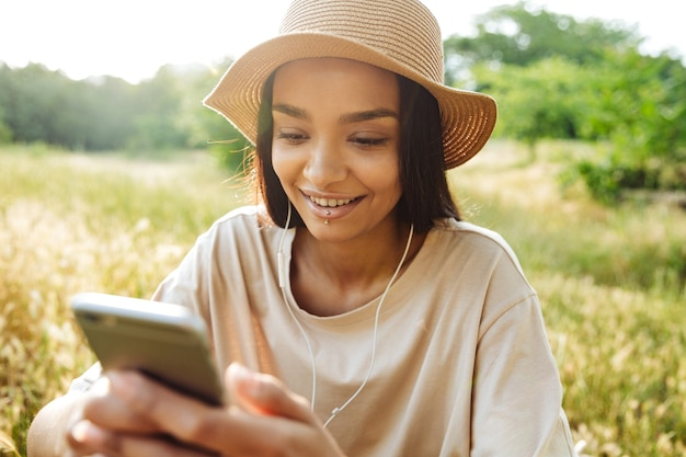 Portret miłej kobiety noszącej przekłuwanie ust za pomocą telefonu komórkowego i słuchawek, siedząc na trawie w zielonym parku