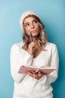 Portret miłej marzącej kobiety w czapce z dzianiny, patrzącej w górę i robiącej notatki w pamiętniku